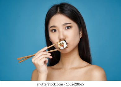 Beautiful woman holds sushi and chopsticks in her hand