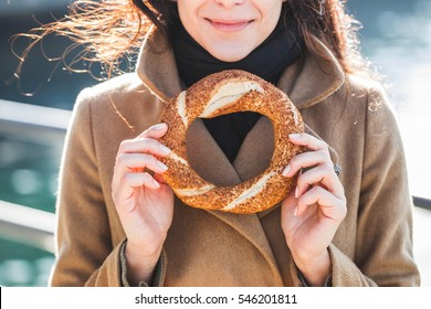 Beautiful woman holds a traditional Turkish simit in hands and wants to eat it