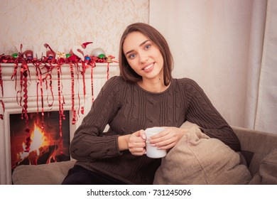 Beautiful woman at home drinking a coffee at the fireplace at christmas time