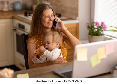 A beautiful woman at home in the kitchen uses a naotbook and tries to work with a small child in her arms and communicate on the phone