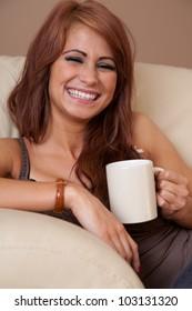 Beautiful woman at home at mug and laughing