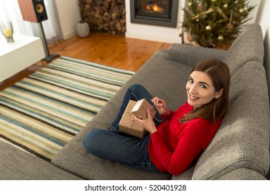 Beautiful woman at home wrapping presents for Christmas