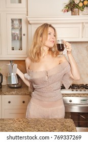 beautiful woman housewife standing in her white kitchen and enjoys strong coffee smell in the morning