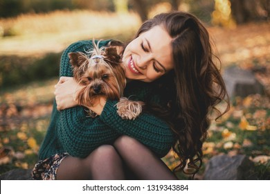 Beautiful woman hugging with dog in the park