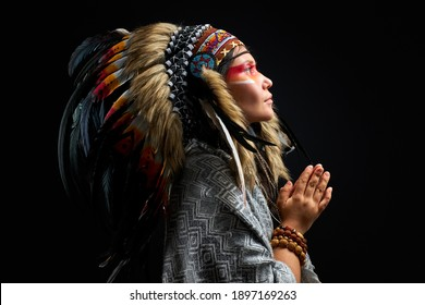 beautiful woman in Indian hat with feathers, accessories Bohemians and Boho, she is looking up, praying. isolated black background