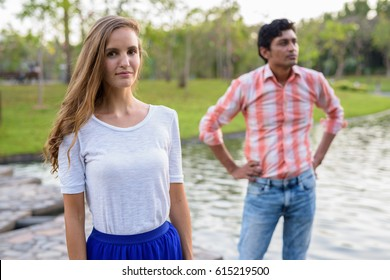 Beautiful woman with Indian man thinking and standing on stone path in the middle of the lake in peaceful green park