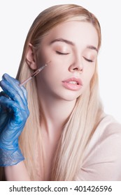 Beautiful woman and injections of youth and beauty, Leather meals, cocktail for the face. Pointing hand gesture