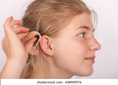 Beautiful woman inserting a hearing aid into her ear