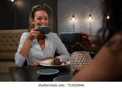 Beautiful woman interacting while having coffee in restaurant