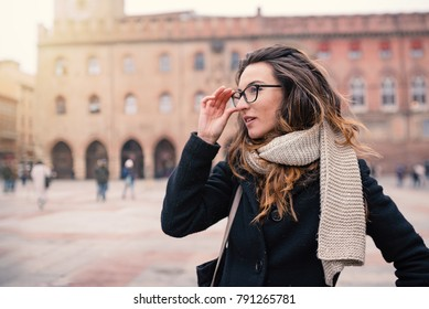 Beautiful woman intimate portrait outdoors in Piazza Maggire, Bologna, Italy. Natual flare.