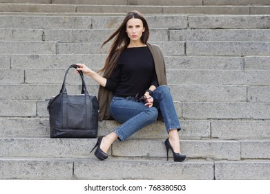 A beautiful woman in jeans, a brown-gray poncho and a black T-shirt with a long sleeve, sitting in the city on stone steps. Points in the hand. Street   fashion, denim style, summer-autumn. black bag.