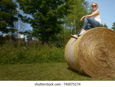 Beautiful woman in jeans sitting on a haystack