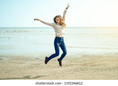 Beautiful woman jeans sweater jumping laughing sea water sun