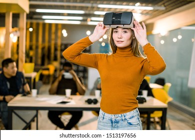 The beautiful woman in jeans and sweater posing with virtual reality goggles at the office. Coworkers team at the table on the background
