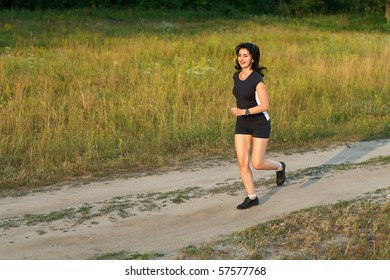 Beautiful woman jogging outdoors in forest road