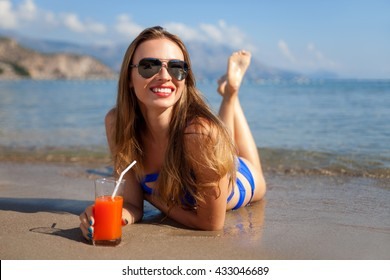 Beautiful woman with juice lying on a sand beach