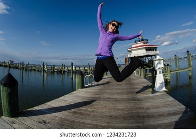 Beautiful woman jumps on a dock alongside the Choptank River Lighthouse in Maryland