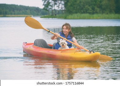 Beautiful woman is kayaking with her dog across the lake