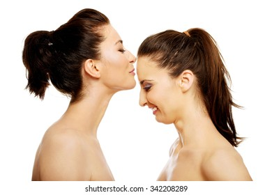 Beautiful woman kissing her friend in forehead.