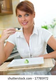 Beautiful woman in kitchen eating using chopsticks