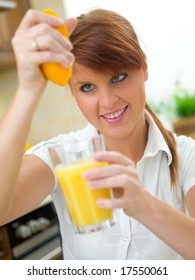Beautiful woman in kitchen squeezing orange to glass