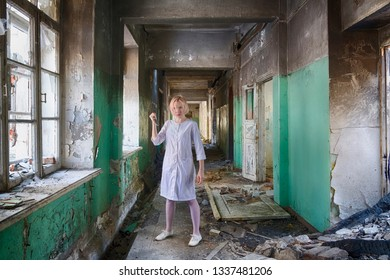 Beautiful woman with knife in white nurse coat (or bathrobe) stand among ruines of abandoned hospital or asylum. Psycho or maniac danger woman