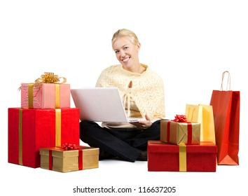 Beautiful woman with laptop surrounded by Christmas presents
