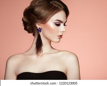Beautiful Woman with Large Earrings Tassels Jewelry Black Color. Perfect Makeup and Elegant Hairstyle. Blue Make-up Arrows