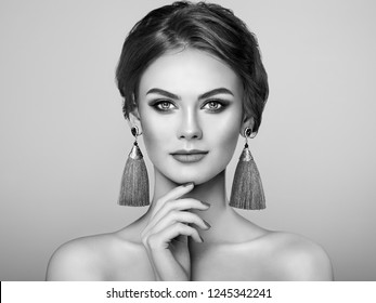 Beautiful Woman with Large Earrings Tassels Jewelry. Fashion  Bijouterie. Perfect Makeup and Elegant Hairstyle. Make-up Arrows. Black and White