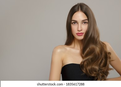 beautiful woman with large wavy hair and makeup. On a gray background