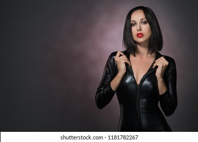 Beautiful woman in latex suit on a dark background