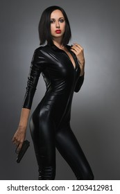 Beautiful woman in latex suit on a dark background with gun