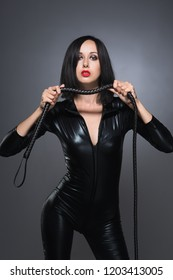 Beautiful woman in latex suit with whip on a dark background