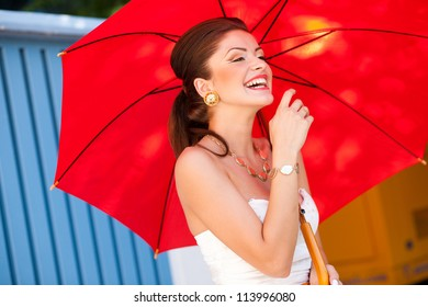 beautiful woman laughing with perfect skin wearing professional make-up holding a red umbrella