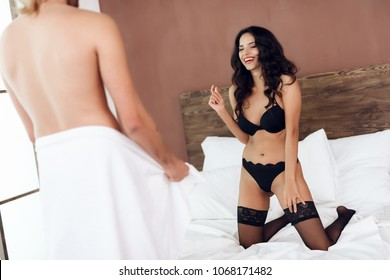 Beautiful woman laughs about size of penis of man who is standing in front of her in bedroom. Small size of manhood. Sexual relations among young people.