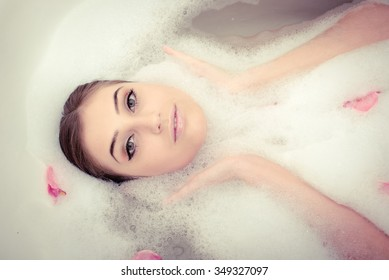 Beautiful woman laying in bubble foam bath with rose petals