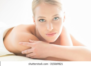 Beautiful woman laying on a mat in beauty salon.