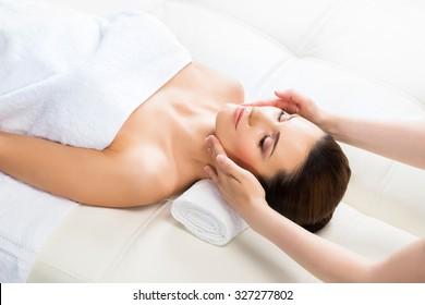 Beautiful woman laying on a mat in massage salon.
