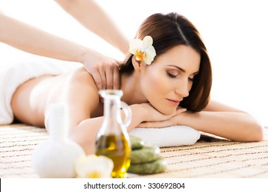 Beautiful woman laying on a mat having a smell of aroma in spa salon.