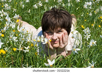 Beautiful woman leaning on her elbows in green grass among the flowers