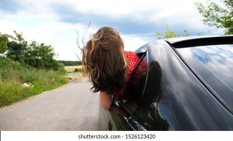 Beautiful woman leaning out of car window and enjoying trip while riding through country road. Young girl looking out of open window moving auto and her long brown hair blowing in wind. Slow motion