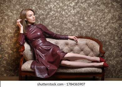 A beautiful woman in a leather dress sits relaxed on the sofa, looking away. Brown background.