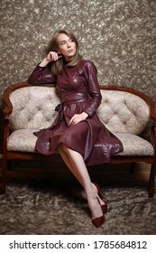 beautiful woman in  leather dress sits thinking on the sofa, looking away. Brown background.