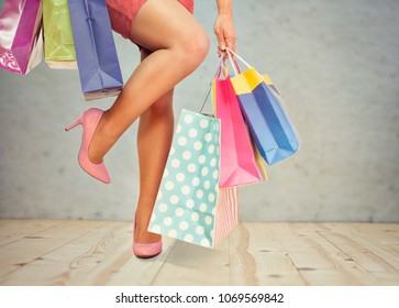 Beautiful woman legs and colorful shopping bags