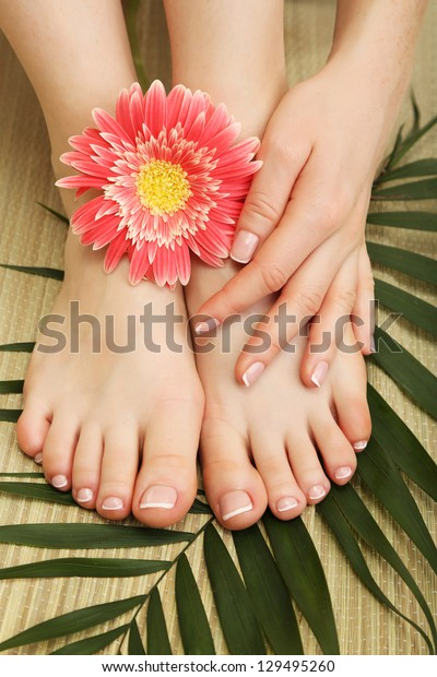 Beautiful woman legs and hand, on bamboo mat