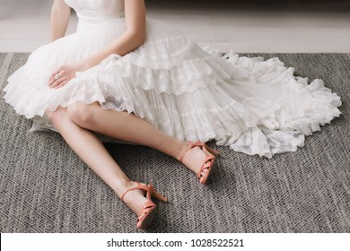 Beautiful woman legs in pink high heel shoes. Wedding dress and shoes. Morning of the bride.