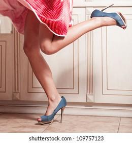Schöne Frauenbeine in rotem Kleid mit blauen High-Ferse-Schuhen