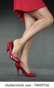 Beautiful woman  legs with red high heel shoes over grey