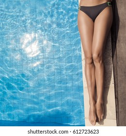 Beautiful woman legs sunbathing near swimming pool.