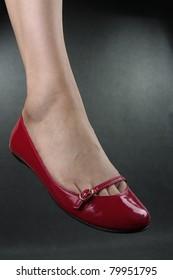 Beautiful woman legs wearing red flat shoes